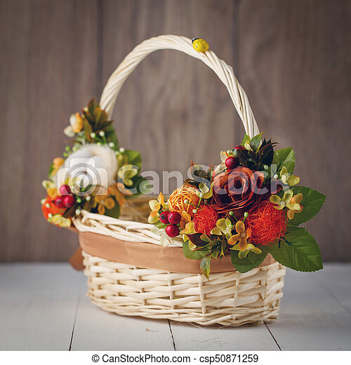 basket with flowers to celebrate Easter on a wooden background - csp50871259