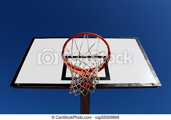 Basketball hoop against blue sky in a playground seen from under the rim (hoop) - csp55509869