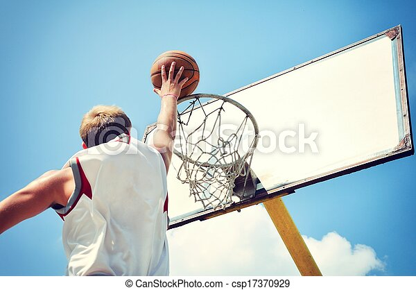 Basketball player in action flying high and scoring - csp17370929