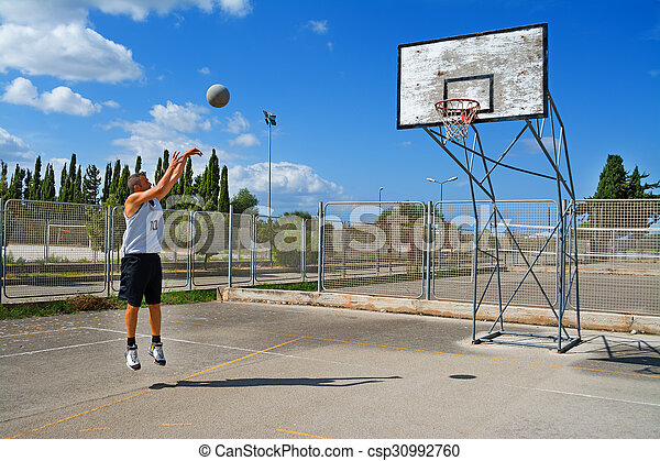 basketball player shooting in a playground - csp30992760