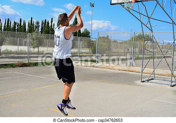 basketball player shooting in a playground - csp34762653