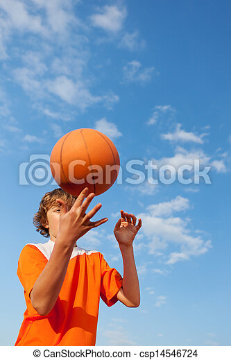 Basketball Player Spinning Ball Against Sky - csp14546724