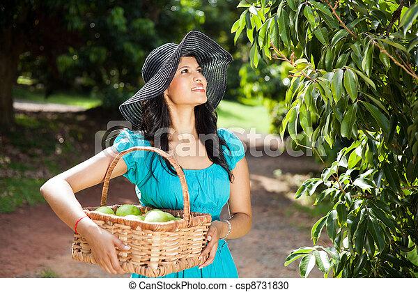 Mujer bonita feliz en el jardín de frutas - csp8731830