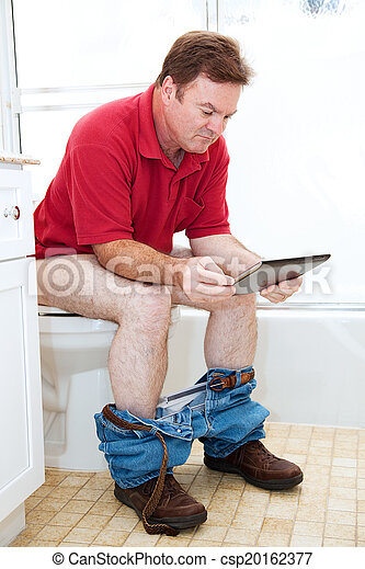 Bathroom toilet reading. Man reading a tablet pc while ...
