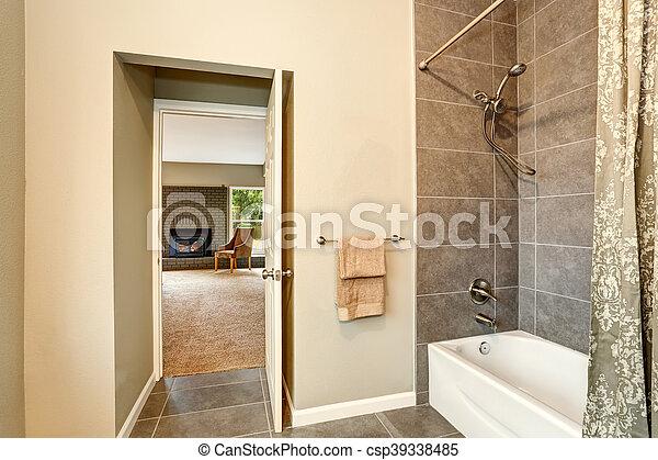 Bathroom with tile trim. view of opened door to bedroom with ...