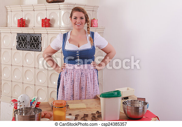 Bavarian girl in dirndl in front of - csp24385357