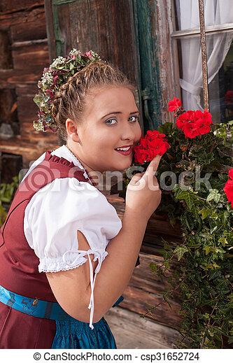 Bavarian girl in dirndl smelling a  - csp31652724