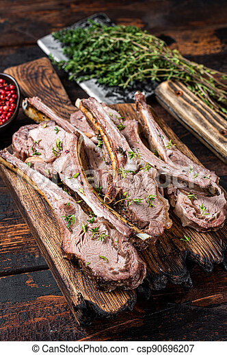 BBQ Grilled Lamb Ribs Chops steaks on butcher board with meat cleaver. Dark wooden background. Top view - csp90696207