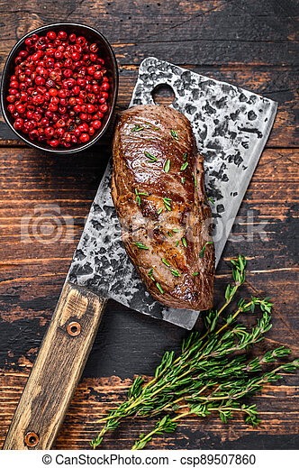 BBQ Grilled veal sirloin meat steak on a meat cleaver with herbs. Dark wooden background. Top view - csp89507860