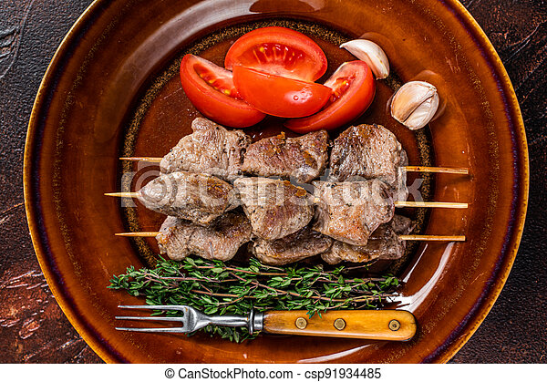 Bbq lamb meat on wooden skewers with vegetables on a rustic plate. Dark background. Top view - csp91934485