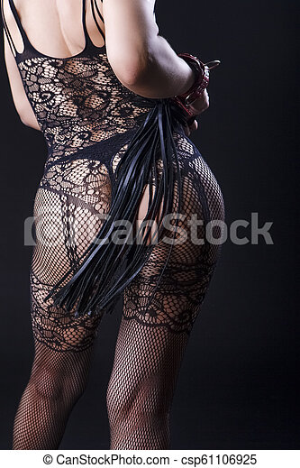 BDSM Concepts and Sex Toys Ideas. Back View of Caucasian Woman in Sexy Lingerie Posing with Leather Lash for BDSM Role Game. - csp61106925
