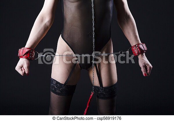 BDSM Concepts. Front View of Mature Caucasian Female Posing with  Accessories for Sado-Masochism Play. Tied with Chain and Wristbands. Against Black. - csp56919176