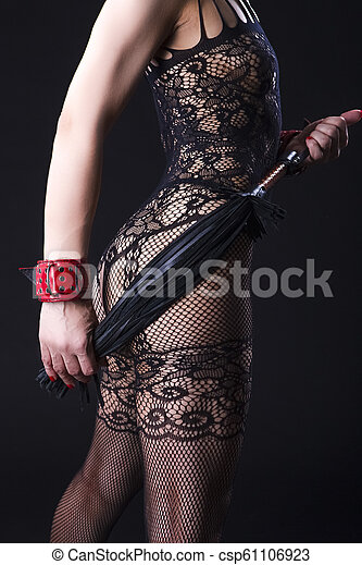 BDSM Concepts, Sex Toys Ideas. Back View of Caucasian Woman in Sexy Lingerie Posing with Leather Lash for BDSM Role Game. - csp61106923