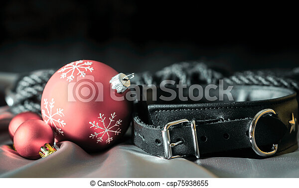 bdsm still life leather collar and christmas balls on silver fabric close up - csp75938655