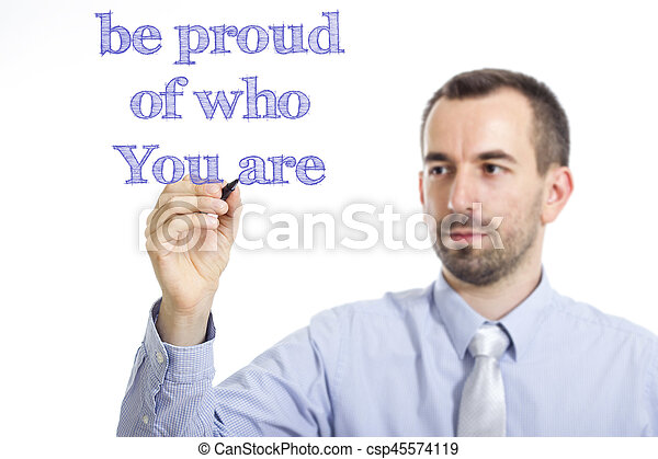 be proud of who You are - Young businessman writing blue text on transparent surface - csp45574119