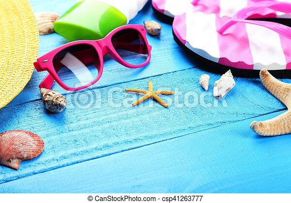 Beach accessories on blue wooden background - csp41263777
