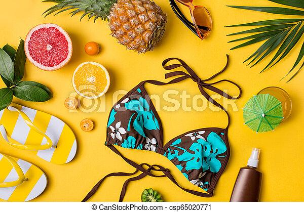 Beach accessories on yellow background - csp65020771