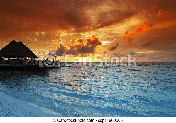 Beach and tropical houses on sunset - csp11960605