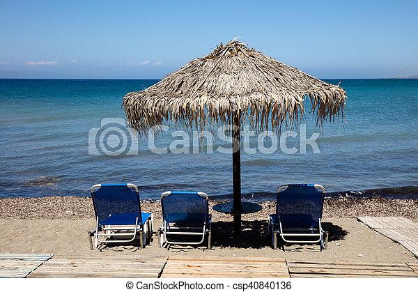 Beach bed and umbrellas - csp40840136