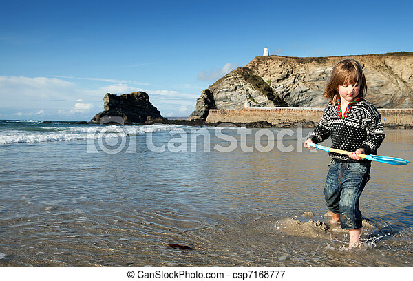 Beach holiday in Cornwall, England. St Agnes coastline with child in water with spade or shovel - csp7168777