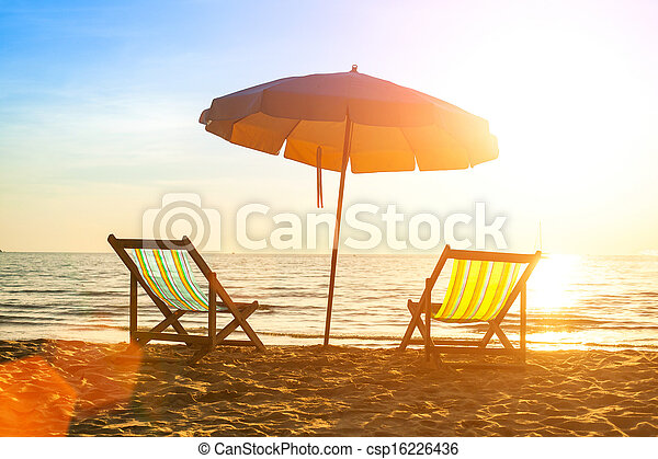 Beach loungers on deserted coast sea at sunrise. - csp16226436