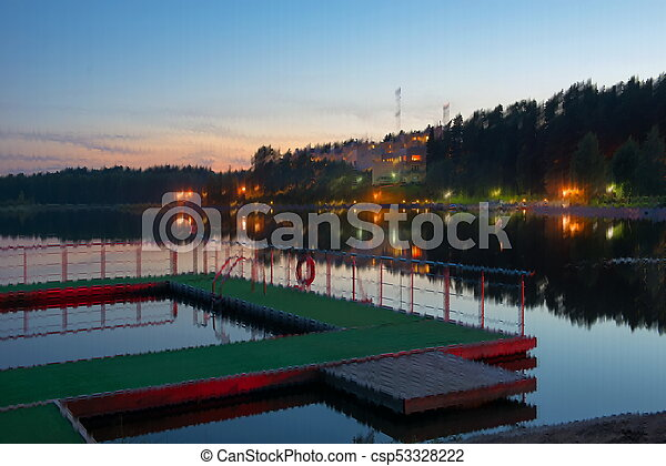Beach on a forest lake at night - csp53328222