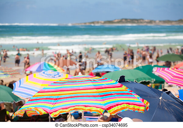 Beach scene with colorful umbrellas and people on the beach - csp34074695
