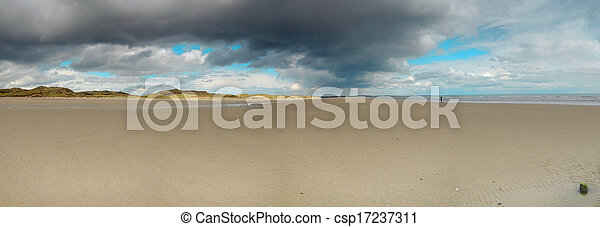 Beach under a dramatic, moody sky panorama - csp17237311