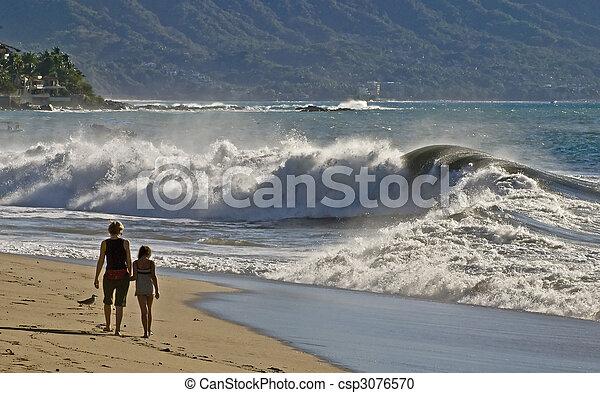 Beach walkers and breaking ocean waves - csp3076570