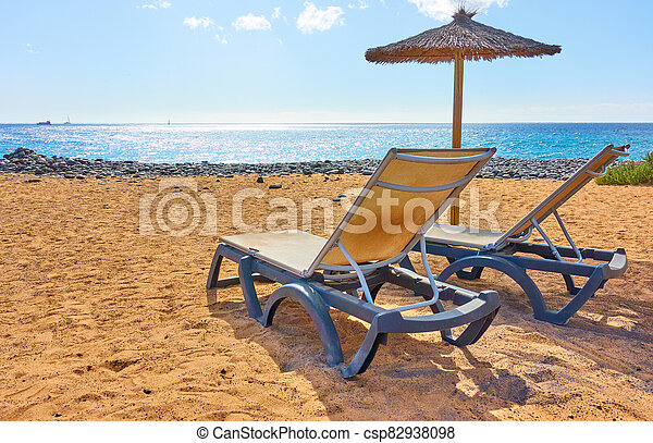 Beach with parasol and chaise longues by the sea - csp82938098