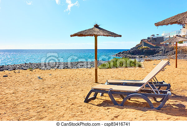 Beach with parasol and sunbeds by the sea - csp83416741