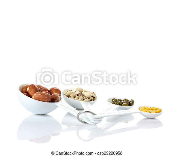 Beans in measuring spoons on white background - csp23220958