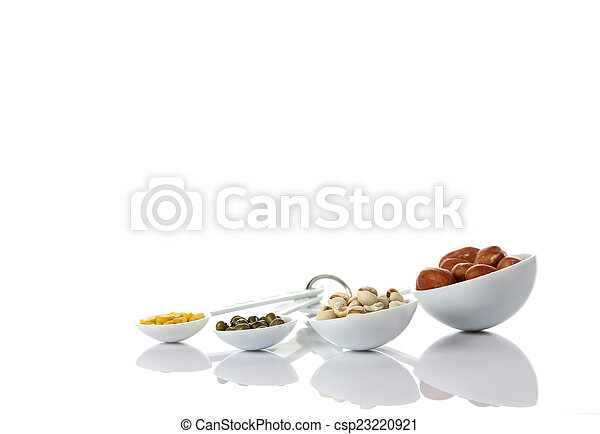 Beans in measuring spoons on white background - csp23220921
