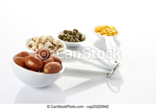 Beans in measuring spoons on white background - csp23220942
