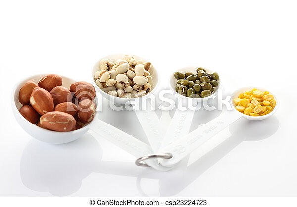 Beans in measuring spoons on white background - csp23224723