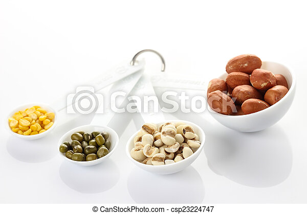 Beans in measuring spoons on white background - csp23224747