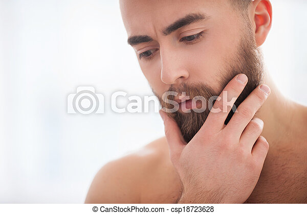 Beard handsome. Portrait of confident young beard man holding hand on chin and looking away - csp18723628