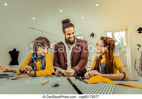 Bearded fashion designer giving master class for children - csp65175077