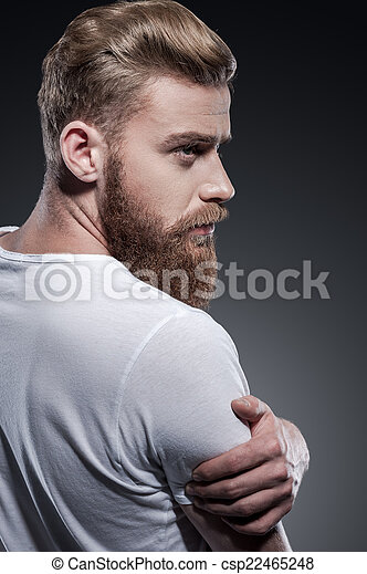 Bearded handsome. Rear view of thoughtful young bearded man looking over shoulder while standing against grey background - csp22465248