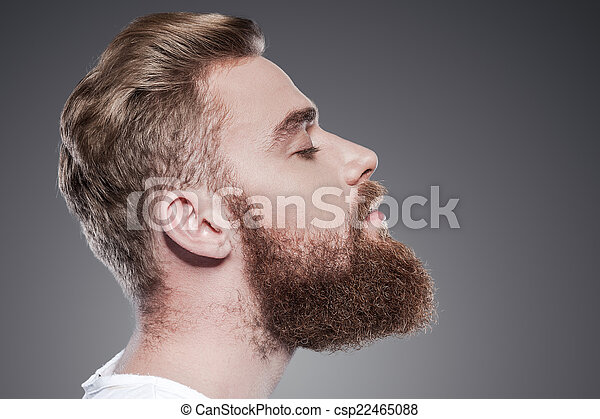 Bearded handsome. Side view of handsome young bearded man keeping eyes closed while standing against grey background - csp22465088