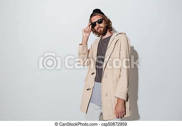 Bearded hipster man wearing sunglasses standing isolated - csp50872959