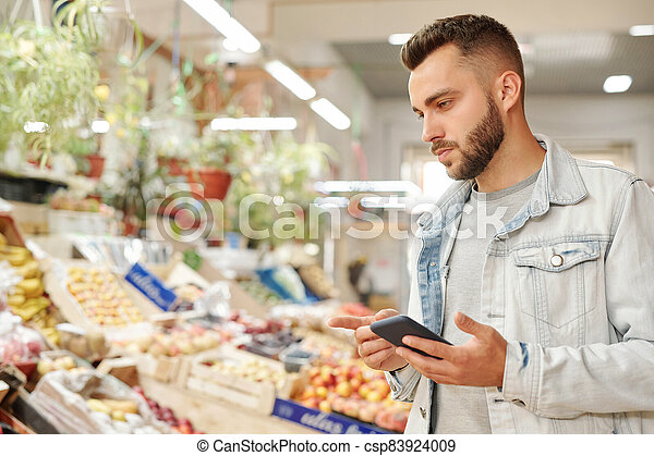 Bearded man checking groceries list - csp83924009
