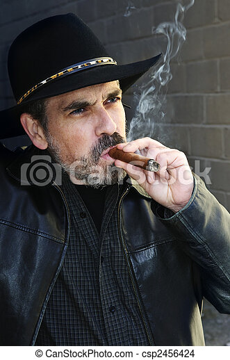 Bearded man smoking cigar - csp2456424