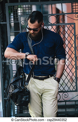 bearded man standing and listening to music - csp29440352