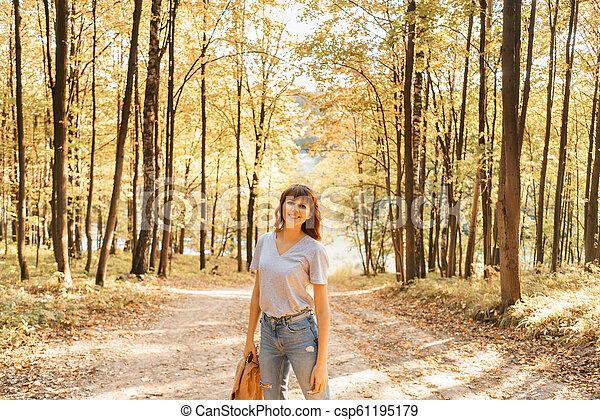 beau, épaules, femme, chandail, light., jeune, arbres, automne, fond, chaud, coucher soleil, jaune, feuillage, portrait, park. - csp61195179