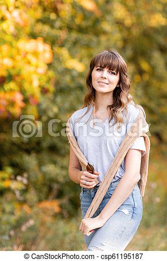 beau, épaules, femme, chandail, light., jeune, arbres, automne, fond, chaud, coucher soleil, jaune, feuillage, portrait, park. - csp61195187