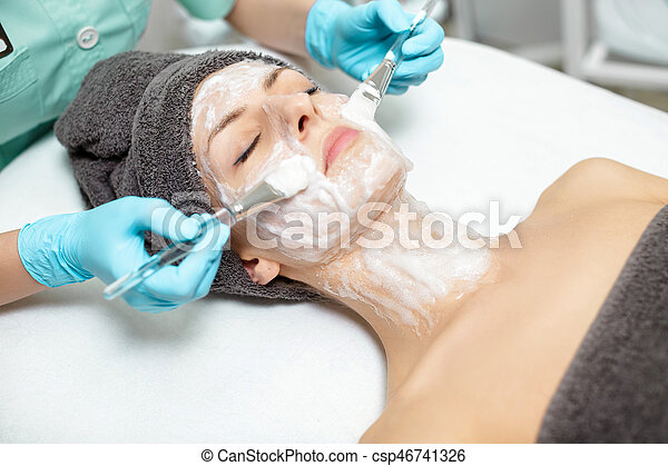 beautician applies face mask on beautiful young woman in Spa salon. cosmetic procedure skin care. Microdermabrasion - csp46741326