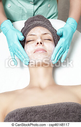 beautician applies face mask to beautiful young woman in Spa salon. cosmetic procedure skin care. Microdermabrasion - csp46148117
