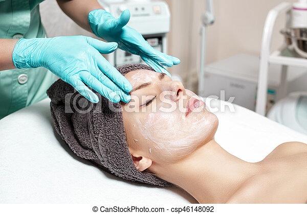 beautician applies face mask to beautiful young woman in Spa salon. cosmetic procedure skin care. Microdermabrasion - csp46148092