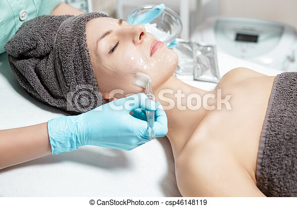 beautician applies face mask with brush to beautiful young woman in Spa salon. cosmetic procedure skin care. - csp46148119